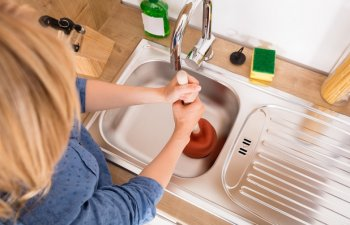 woman unclogging a sink in the kitchen